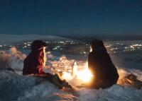 Två personer kring öppen eld i vinternatten.