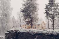 Herrgårdsbyggnad omgiven av vinterlandskap.