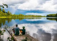 Far och son sitter på brygga vid en sjö.