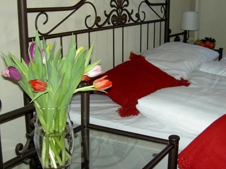Double bed with tulips on the bedside table.