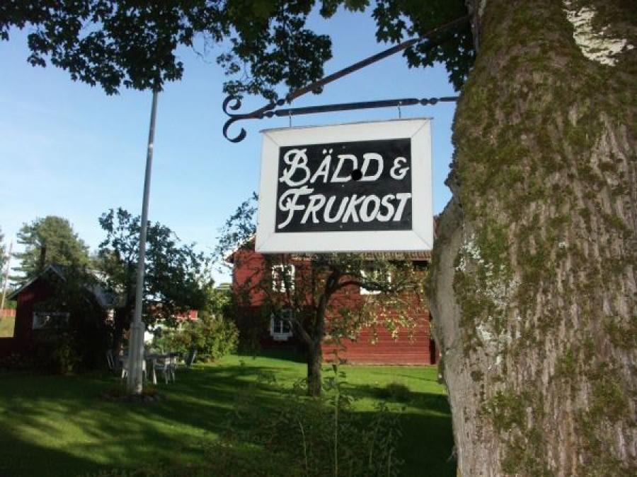 A sign saying bed and breakfast in front of the house.