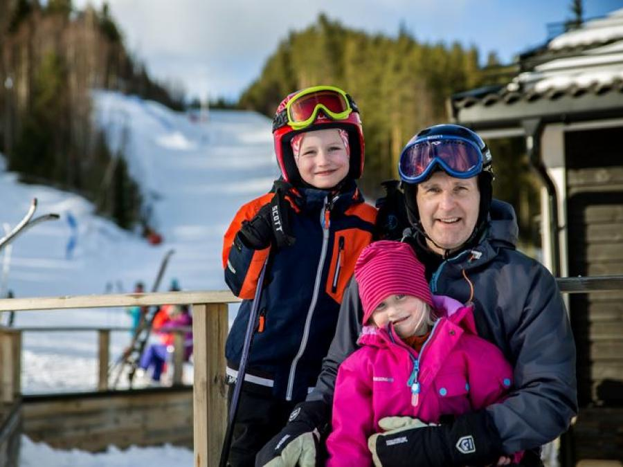 Man and two children (girl and a boy) wearing ski chlotes, ski slope in the background.
