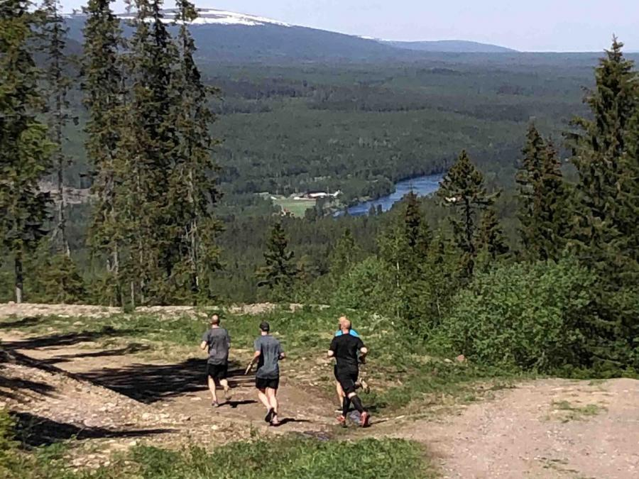 Three people are running along a trail with a view of mountains, forest and water.